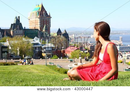 Quebec City scape with Chateau Frontenac and young woman in red summer dress sitting in grass enjoying the view. Tourist or student in Quebec City, Quebec, Canada.