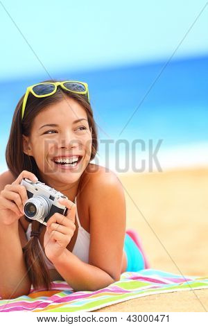 Summer beach woman fun holding vintage retro camera laughing and smiling happy during summer holiday vacation travel.