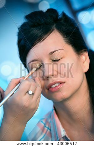 Young happy beautiful woman with makeup brush