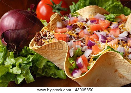 Taco salad in freshly baked flour tortilla bowl (seasoned ground beef, lettuce, onions, tomatoes, and shredded cheese) with tomato, onion, and leaf lettuce in background.  Macro with shallow dof.