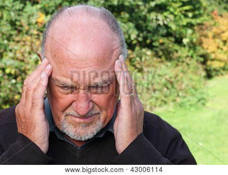 A senior man suffering from a headache or migraine
