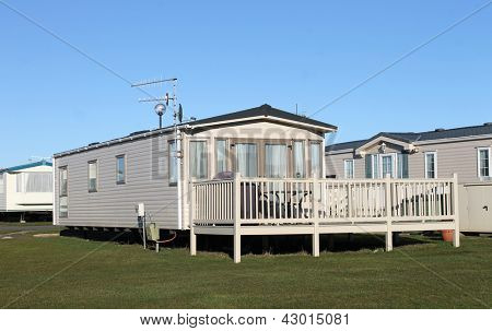 Modern static caravans in park with blue sky background.