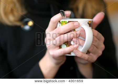 Holding A Cup Of Hot Drink.