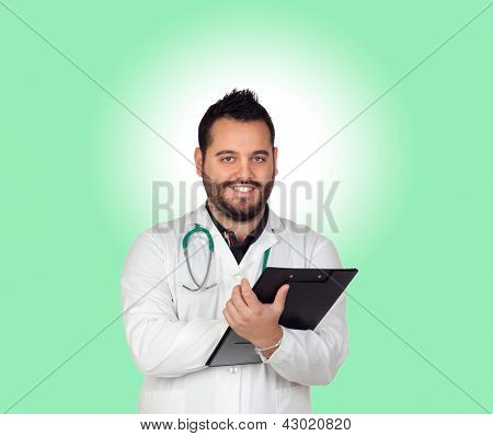 Bearded young doctor with a clipboard isolated on green background