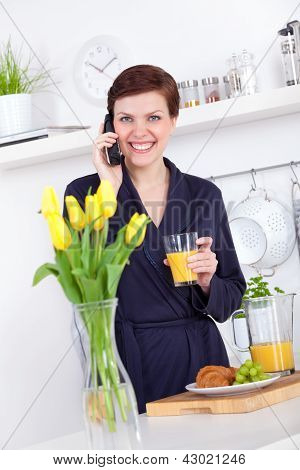 Woman Drinking A Glass Of Orange Juice And Talking On The Phone