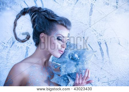 Beautiful sexy, glamorous girl with drawings on the body in an image of the queen of winter. Blue toning