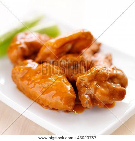 plate of buffalo wings with celery closeup
