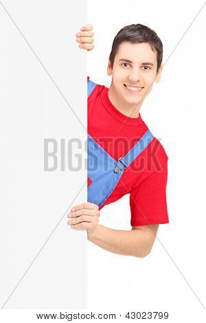 Repairman smiling and posing behind a white panel isolated against white background