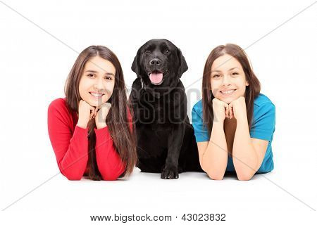 Two young females lying and posing with a dog