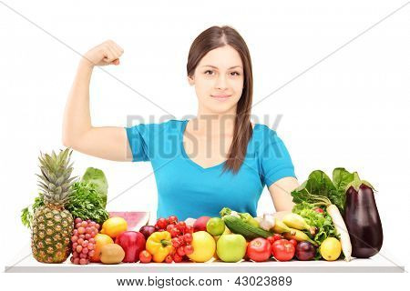 Healthy young female showing her arm muscle and sitting behind a pile of fruits and vegetables