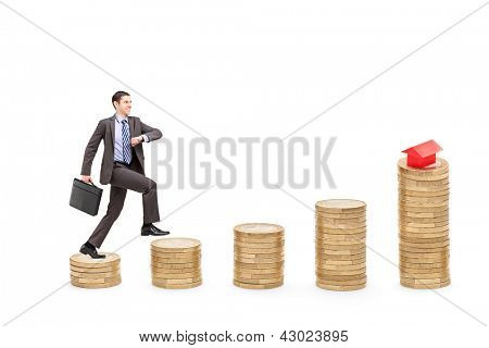 Full length portrait of a businessman with a briefcase walking over piles of coins towards a model house isolated on white background