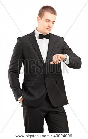 A young man in black suit with bow tie looking at wrist watch isolated on white background