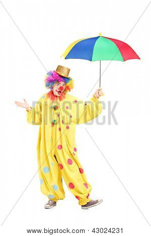 Full length portrait of a cheerful clown holding a colorful umbrella isolated on white background
