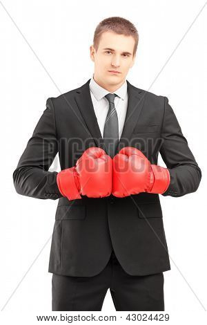 Handsome man in black suit with red boxing gloves posing isolated on white background