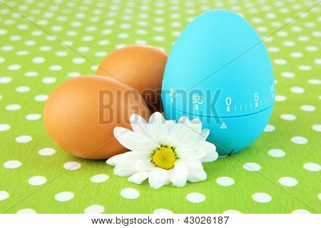 Blue egg timer and eggs, on color background