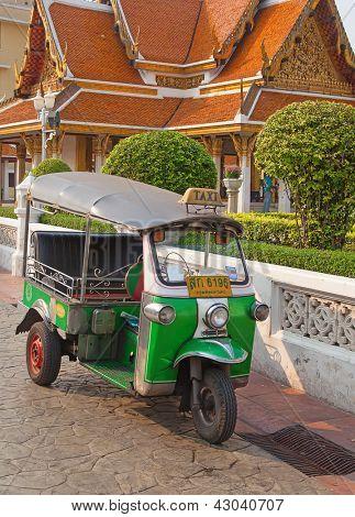 BANGKOK - FEBRUARY 20: Tuk-tuk moto taxi on the street near Wat Saket temple on February 20, 2012 in Bangkok. Famous bangkok moto-taxi called tuk-tuk is a landmark of the city and popular transport.