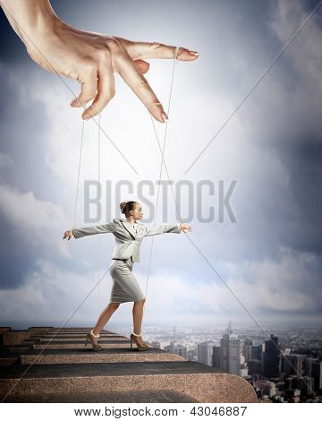 Businesswoman marionette on ropes controlled by puppeteer against city background