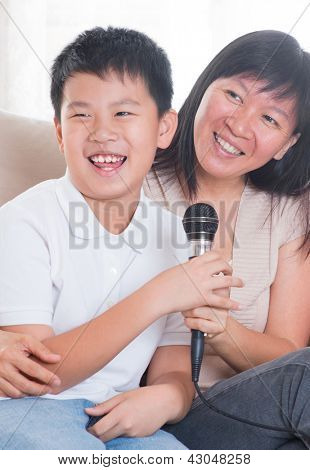 Southeast Asian family living lifestyle. Portrait of a happy Asian family singing karaoke through microphone in the living room