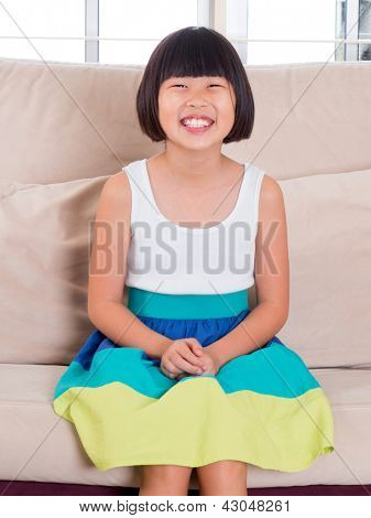 Seven years old Southeast Asian child sitting on sofa at home with happy face