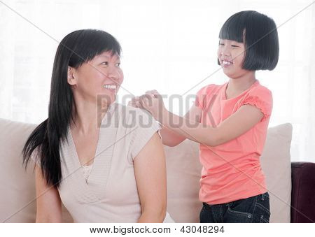 Filial piety concept. Southeast Asian child doing shoulder massage to her mother at home.