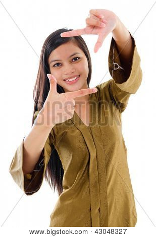 Smiling Southeast Asian Muslim female in traditional kebaya with long black hair making a frame by fingers standing isolated on white background.