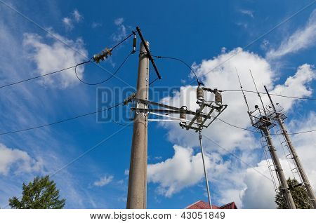 Electric Power Post With Wire Against Bright Blue Sky And Clouds