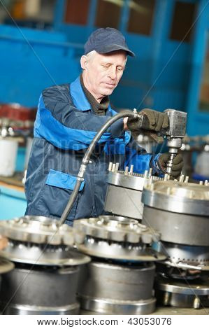 adult experienced industrial worker during heavy industry machinery assembling on production line manufacturing workshop