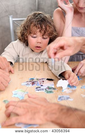 Little boy playing with pictures at a table