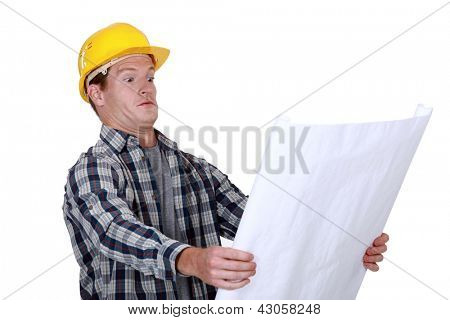 craftsman holding a blueprint and looking very surprised