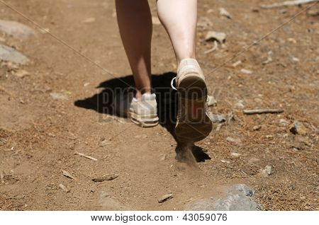 Centered close up of woman's feet hiking in dirt