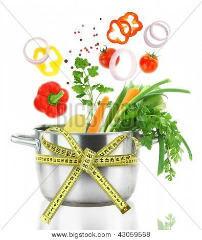 Fresh vegetables falling into a casserole pot with measuring tape