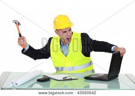 Arquiteto despedaçar seu laptop com martelo