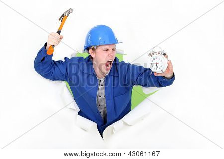 Angry man holding a hammer and an alarm clock
