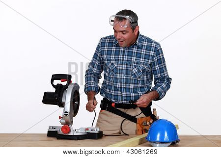 Astonished man looking at a mitre saw