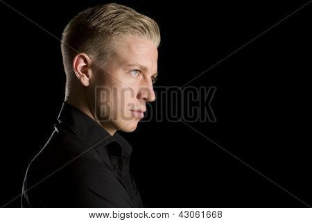 Side-face low key portrait of young handsome man in dark shirt looking up, isolated on black background.