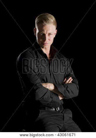 Low-key portrait of confident seductive man in dark shirt looking straight, isolated on black background.
