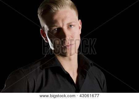 Low-key portrait of young handsome man in dark shirt looking straight, isolated on black background.