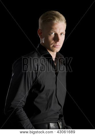 Low-key portrait of serious charming man in dark shirt looking straight, isolated on black background.