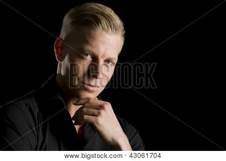 Low-key portrait of young charming man in dark shirt with hand at chin looking straight, isolated on black background.