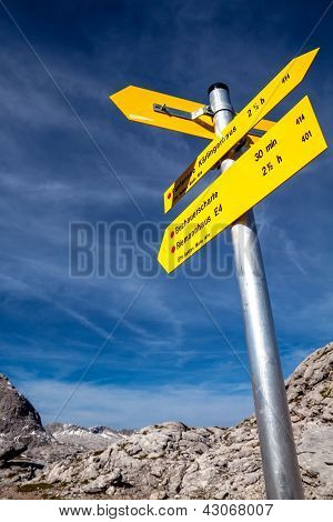 Yellow sign-board against mountain scenery