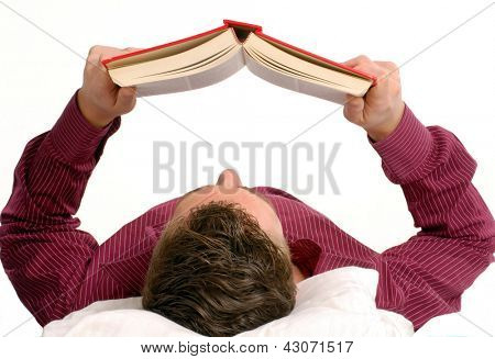 Young man lying down reading a book on bed.