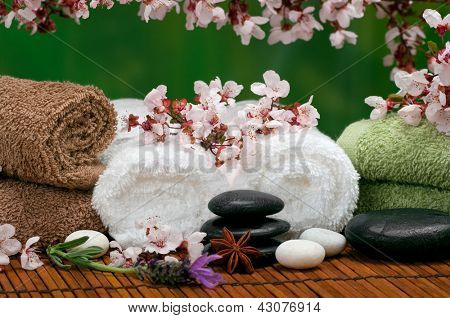 Spa scene with pebbles, lavender, towels and cherry blossoms
