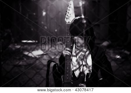 Young female guitarist behind grid fence.