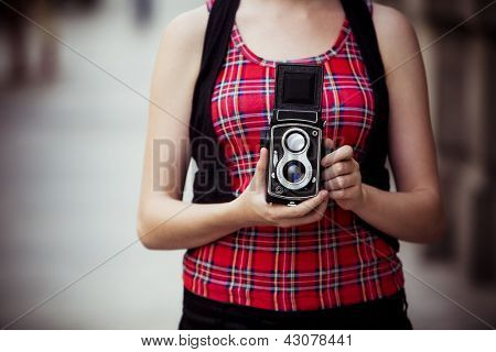 Young urban unrecognizable vintage photographer with old 6x6 camera.