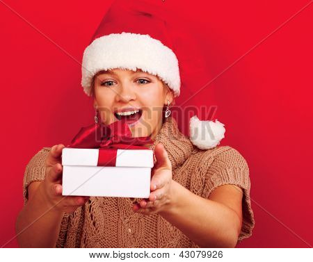 A smiling woman on santa hat with christmas gifts, isolated on red background