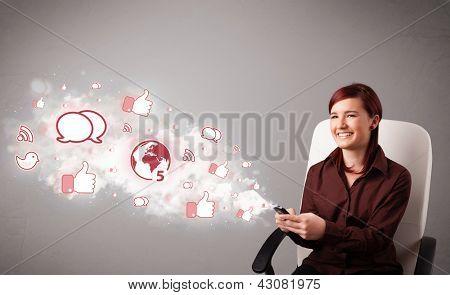 Bastante joven sosteniendo un teléfono con iconos de redes sociales en nube Resumen