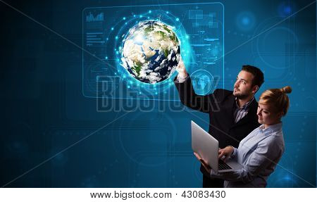 Happy young couple touching high-tech 3d earth panel