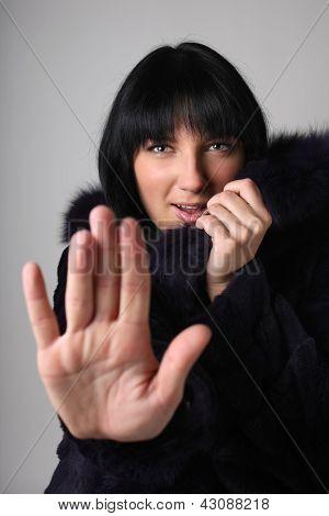 Young Woman In Fur Coat Making Stop Gesture
