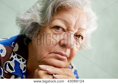 Portrait Of Serious Old Woman Looking At Camera With Hands On Chin