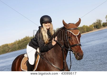 Happy female rider leaning over horse caressing back at riverside.